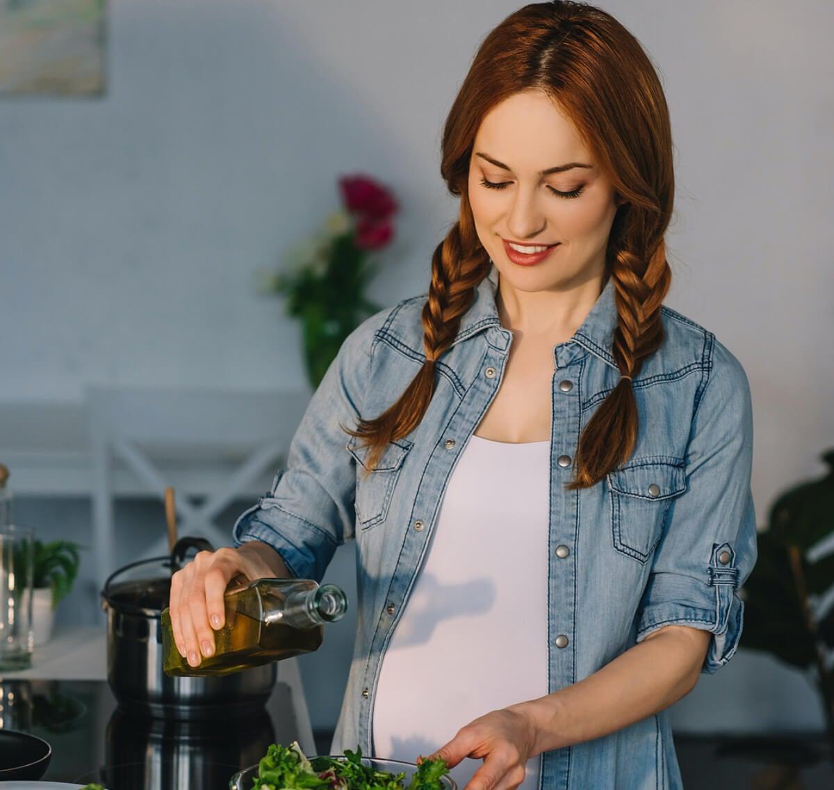 Mujer embarazada echando aceite de oliva a su ensalada.