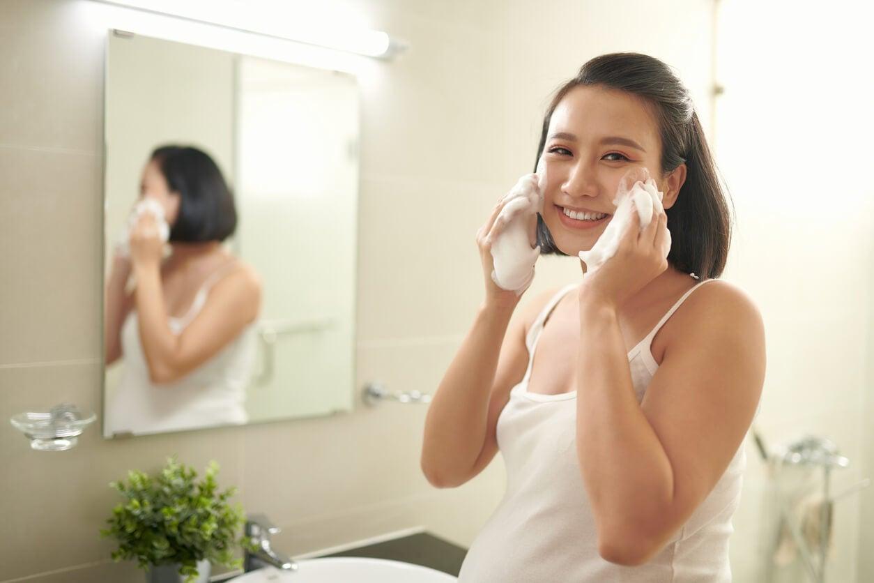 Mujer limpiando su rostro como parte de su rutina de belleza diaria durante el embarazo.