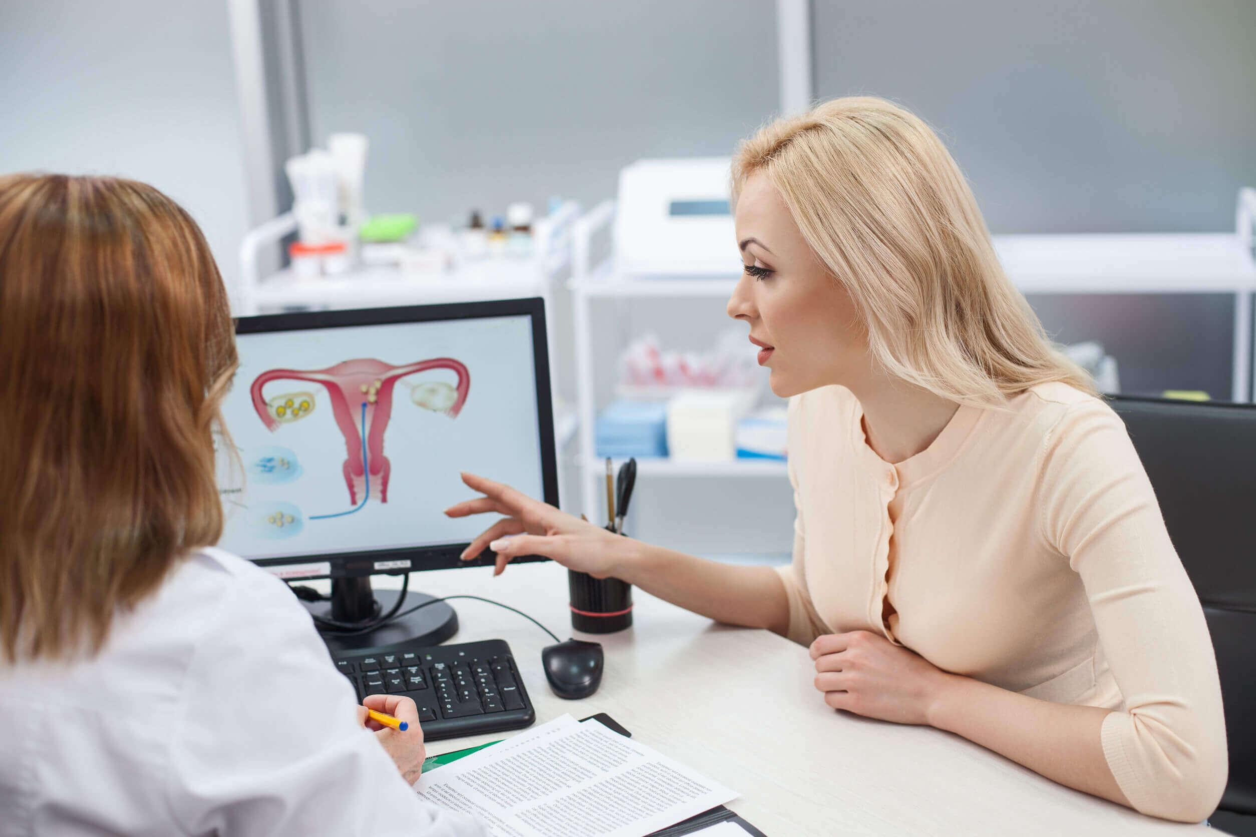 Mujer en el ginecólogo aprendiendo sobre el tamaño de la barriga y el útero durante el embarazo.