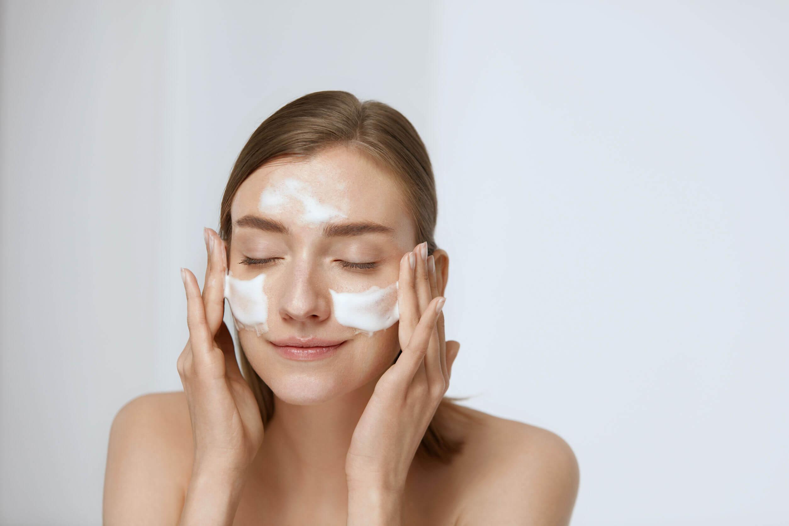 Mujer aplicando una crema hidratante como parte de la rutina facial para embarazadas.