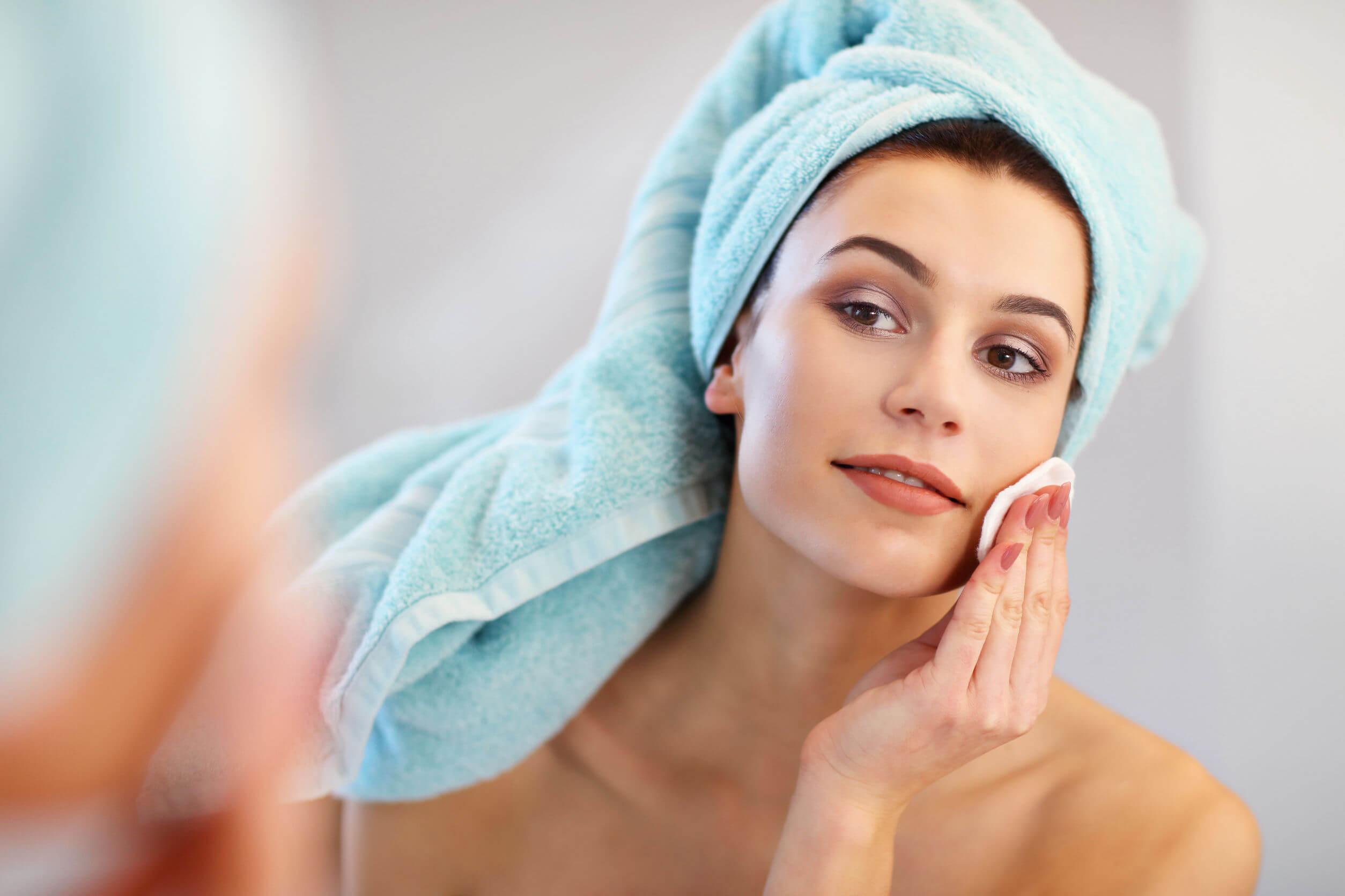 Mujer embarazada limpiando los restos de maquillaje de su cara con un disco de algodón.