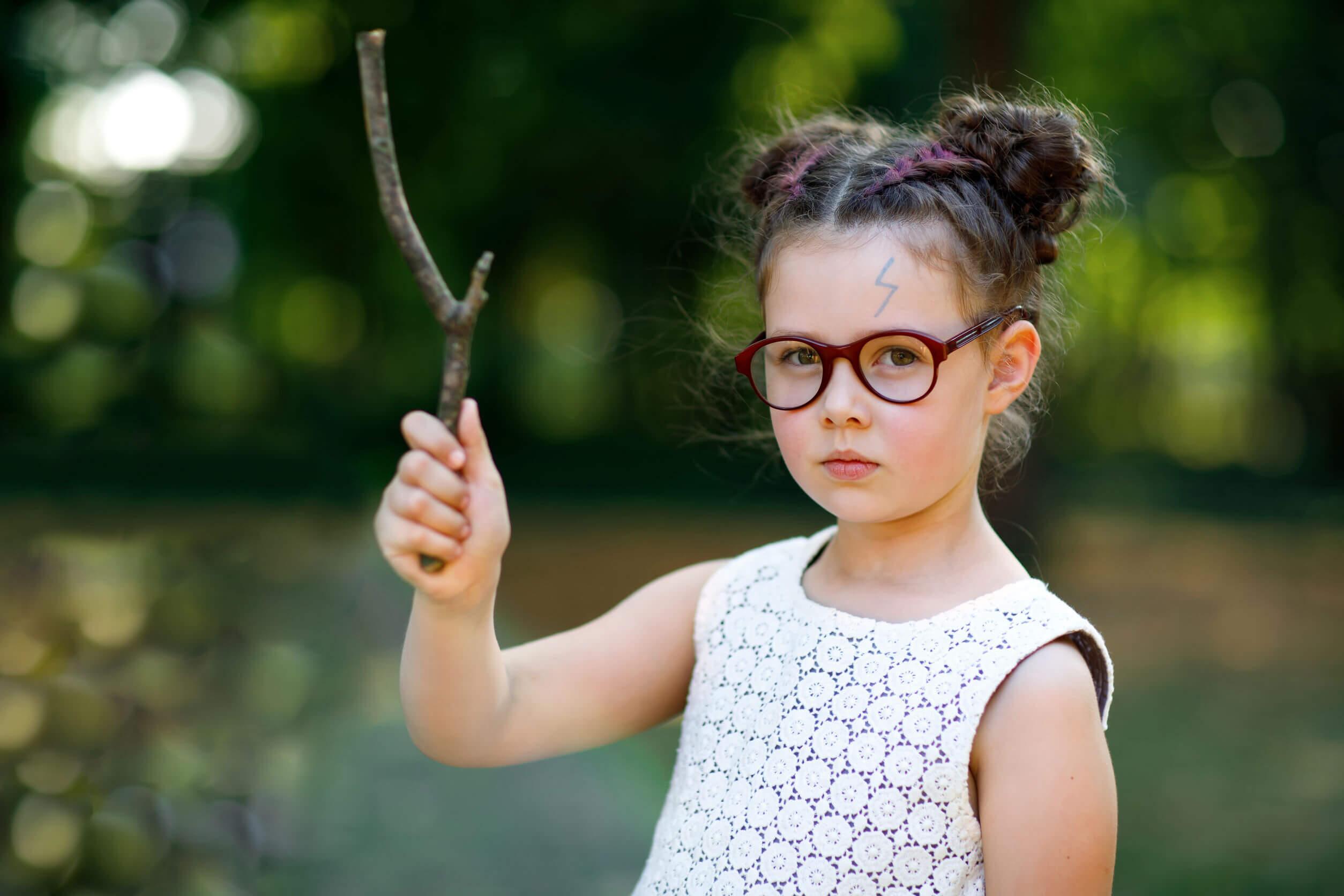 Niña disfrazada de Harry Potter con una varita hecha con un palo.