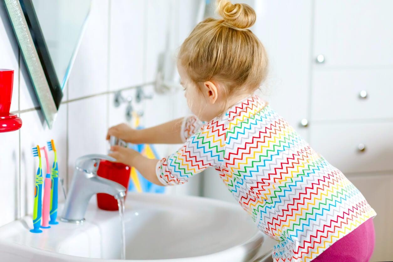 Niña lavándose las manos.