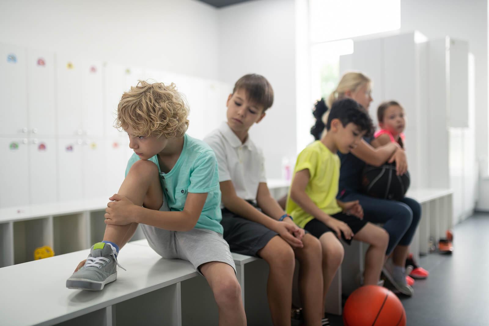 Niño en el vestuario sufriendo acoso en el deporte.