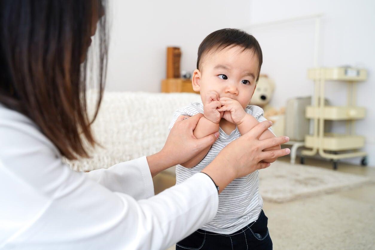 Niño pequeño llevándose las manos a la boca.