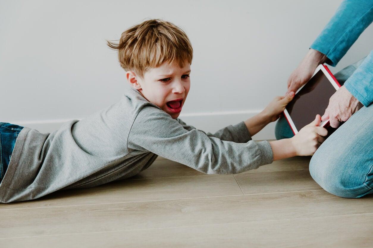 Niño gritando porque su madre le ha quitado la tablet porque sufre estrés digital.
