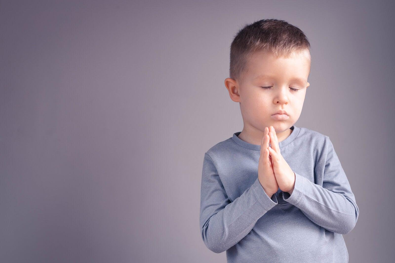 Niño meditando sobre su paz interior.