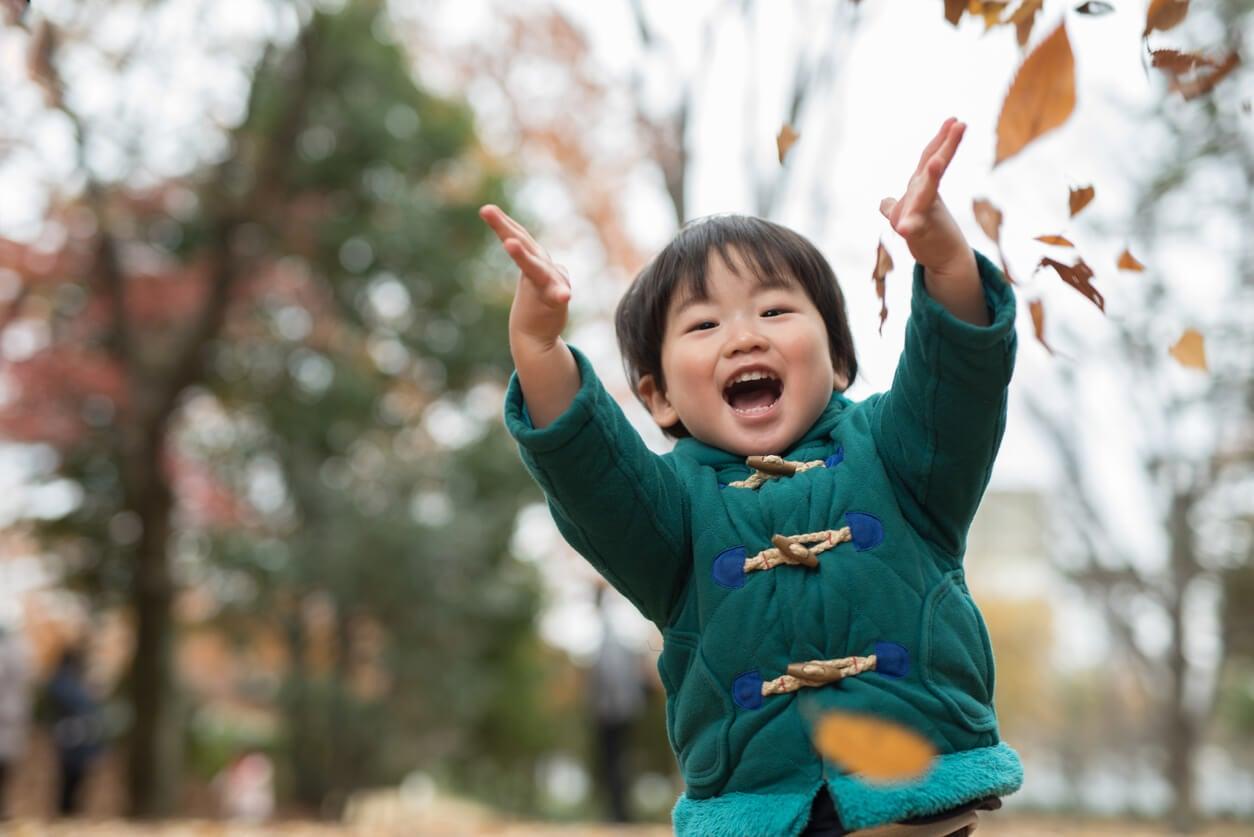 Niño de 3 años jugando con las hojas en el parque.