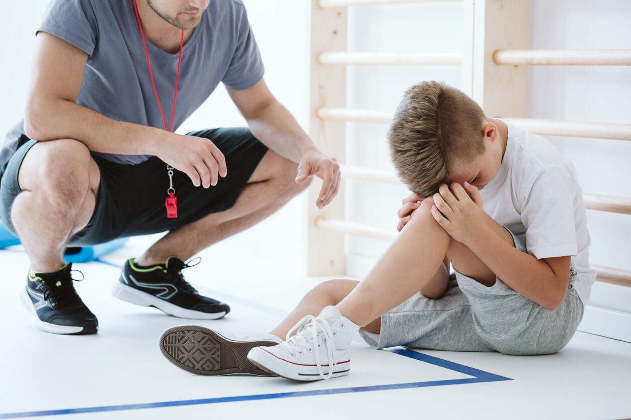 Entrenador dando ánimos a un chico que siente ansiedad por el rendimiento deportivo.