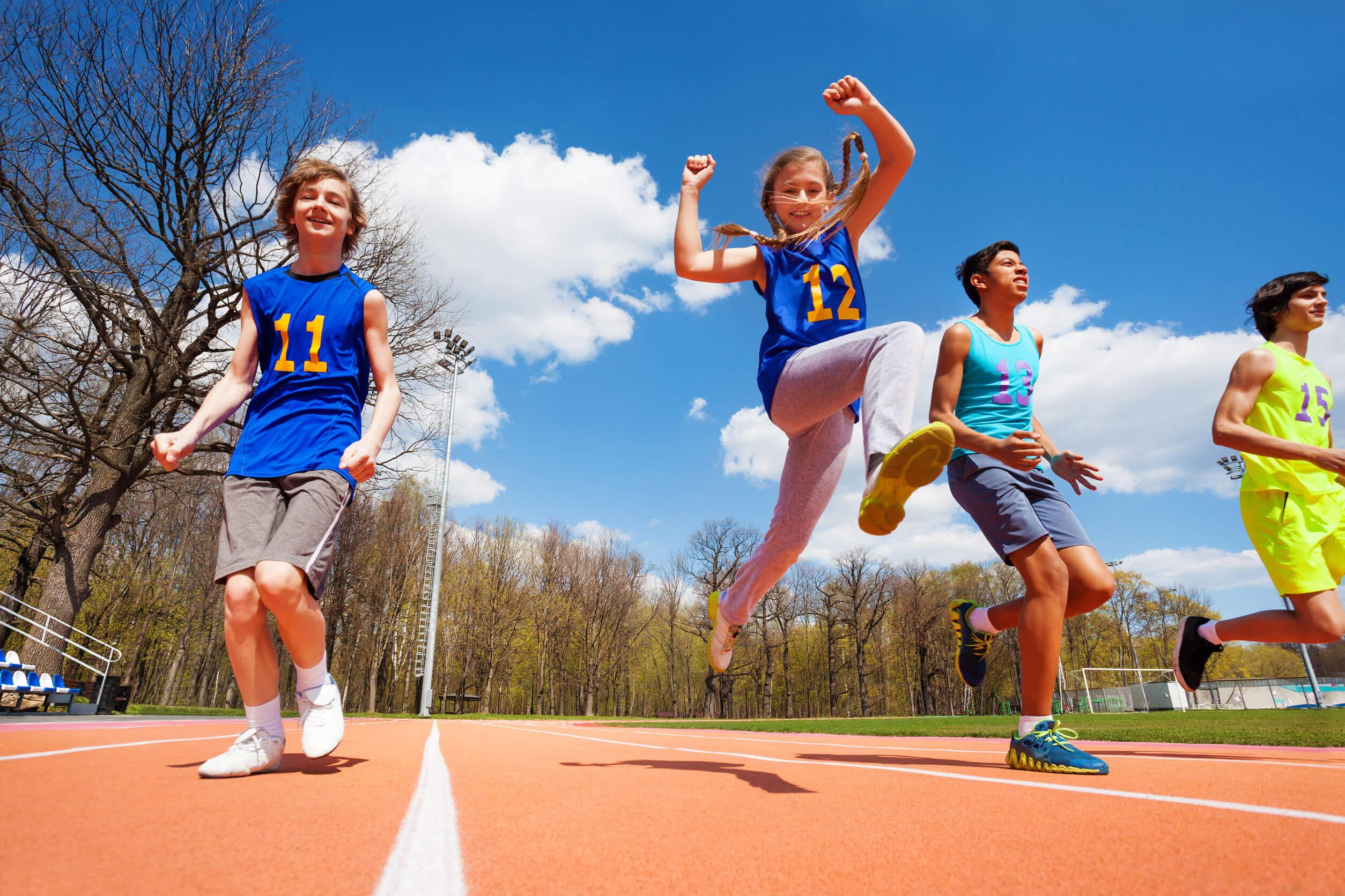 Niños practicando atletismo con deportividad.