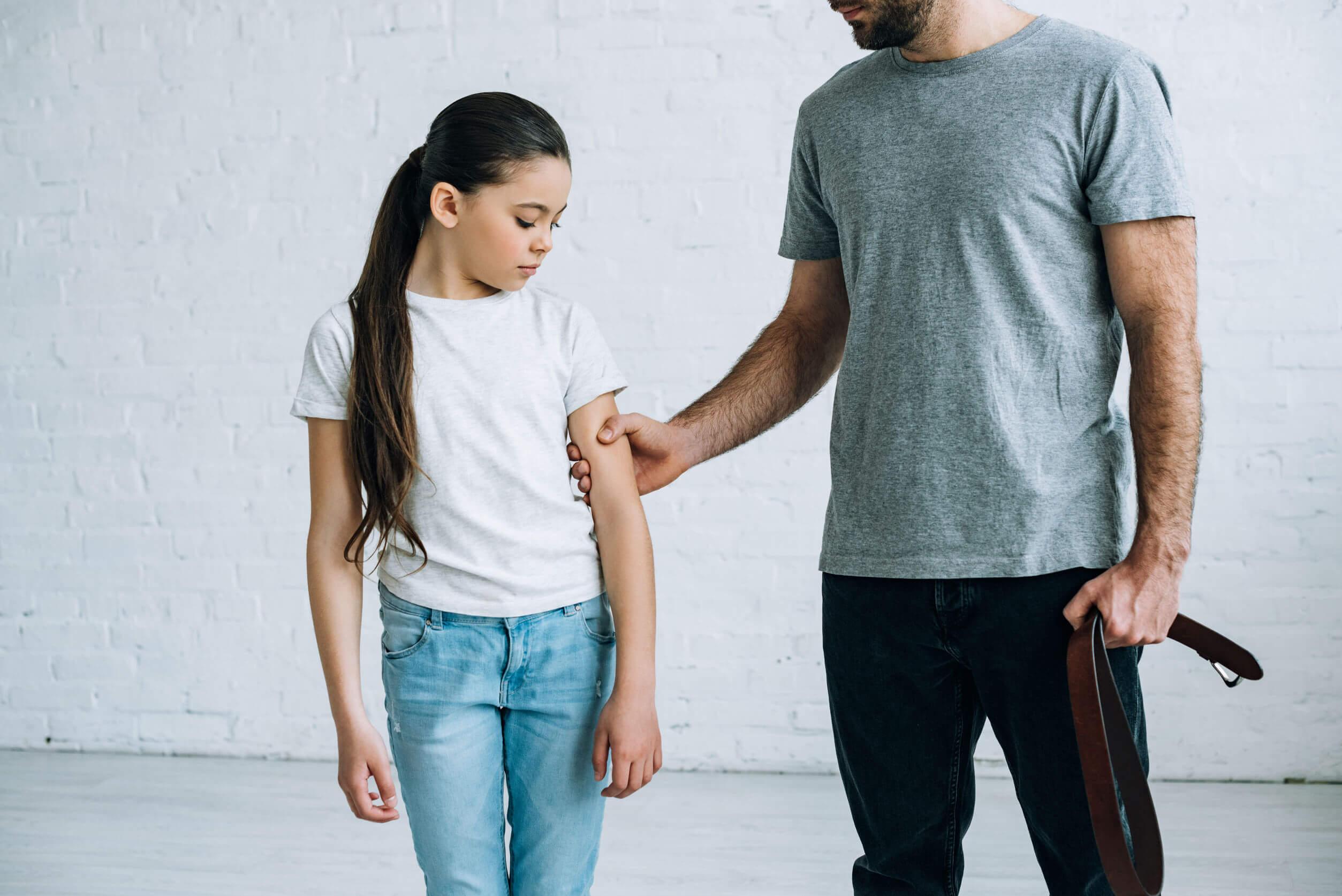 Padre aplicando el castigo físico con su hija.