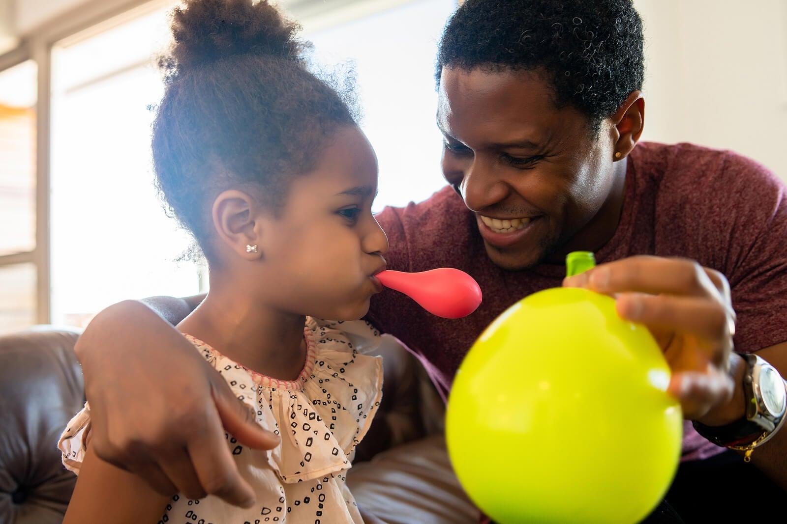 Padre e hija jugando con globos en casa.