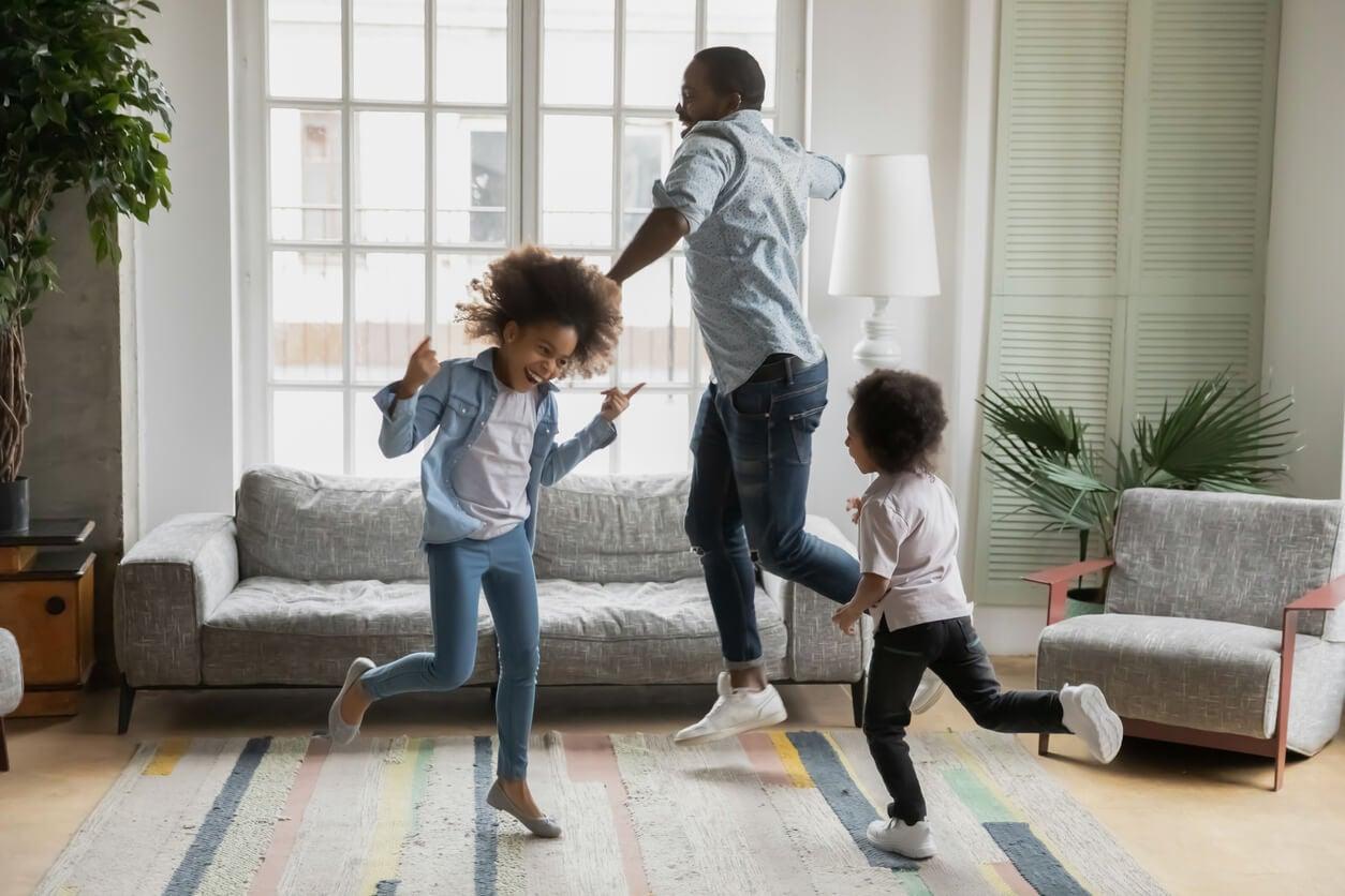 Padre bailando con sus hijos en el salón de casa.