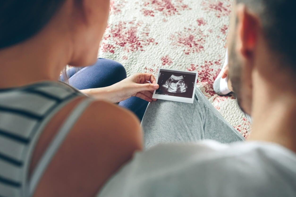 Futuros padres mirando una ecografía y pensando en nombres de niño que empiecen por la letra A.