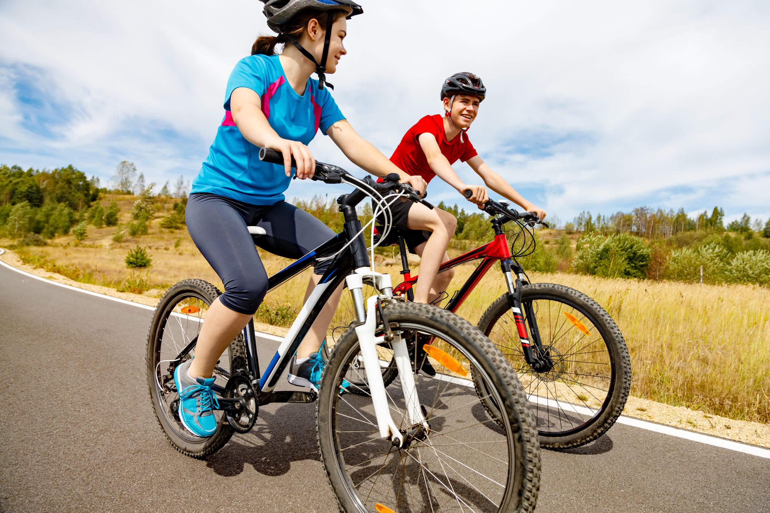 Adolescentes montando en bicicleta porque conocen los beneficios del deporte en la adolescencia.