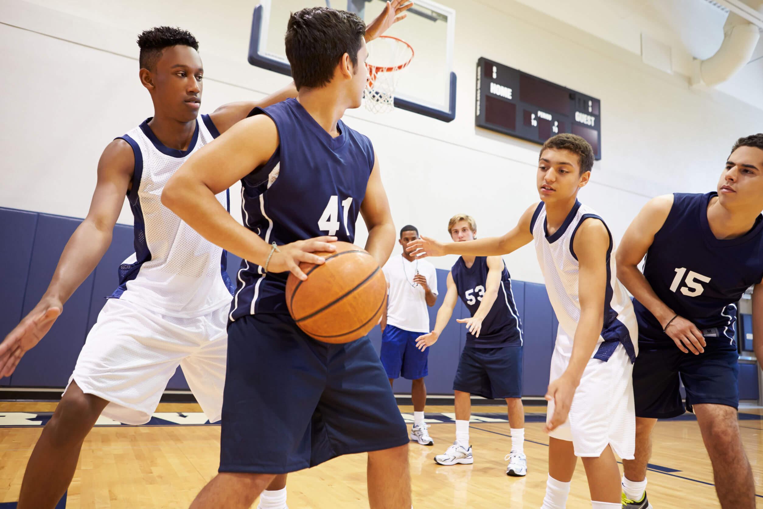 Adolescentes jugando en un equipo de baloncesto.