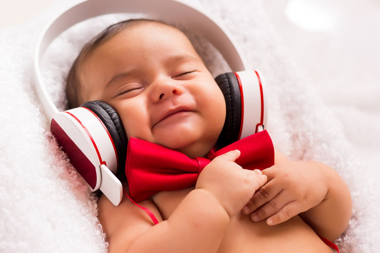 Niño escuchando música con auriculares porque los sonidos influyen en el cerebro de los bebés.
