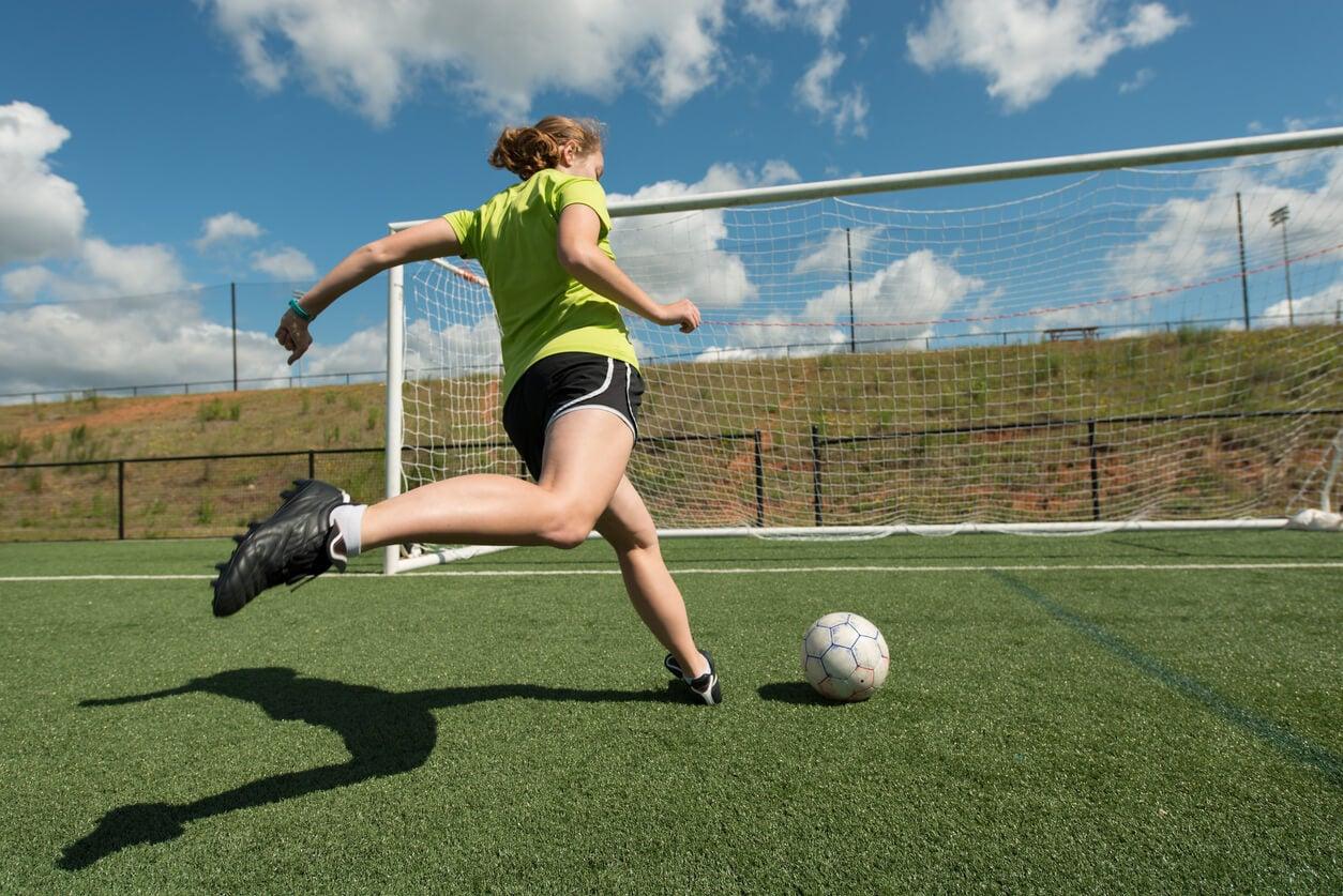 Chica adolescente jugando al fútbol.