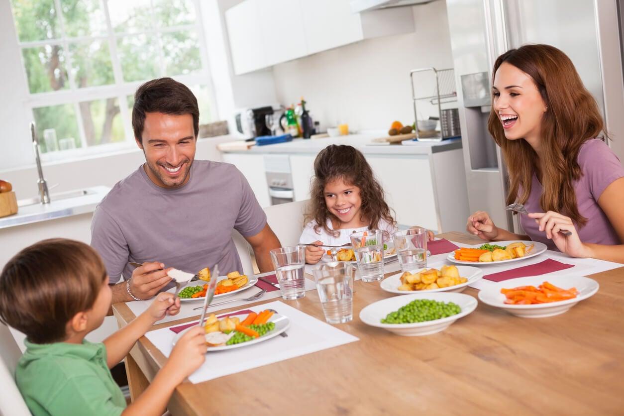 Familia comiendo en la mesa de la cocina.