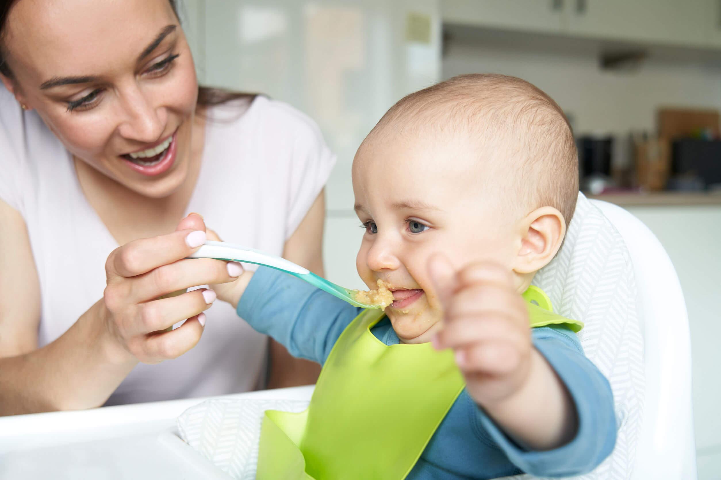 Madre alimentando a su hijo para prevenir los problemas de masticación.