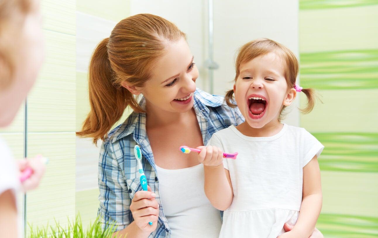 Madre con su hija enseñando a su hijo a cepillarse los dientes y los diferentes cepillos de dientes para niños.