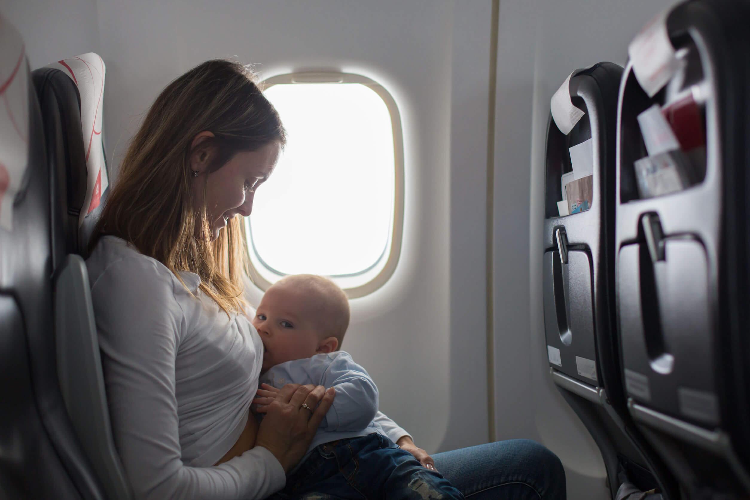 La donna allatta suo figlio su un aeroplano.