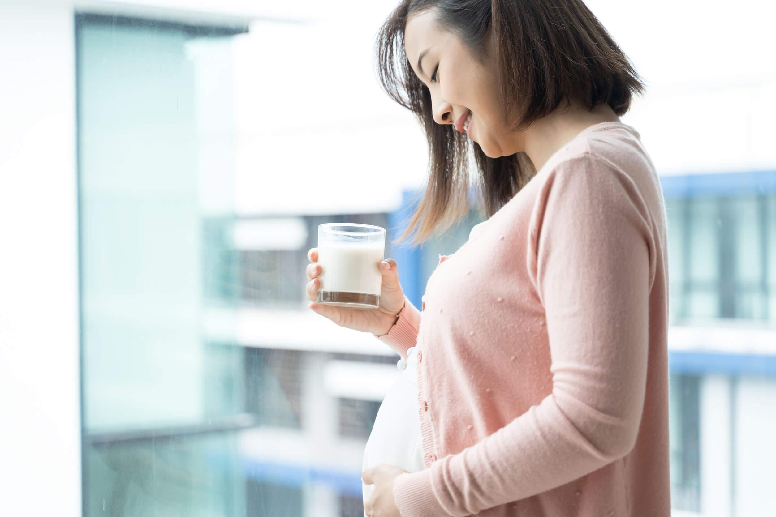 Mujer embarazada bebiendo leche para reducir los ardores estomacales.