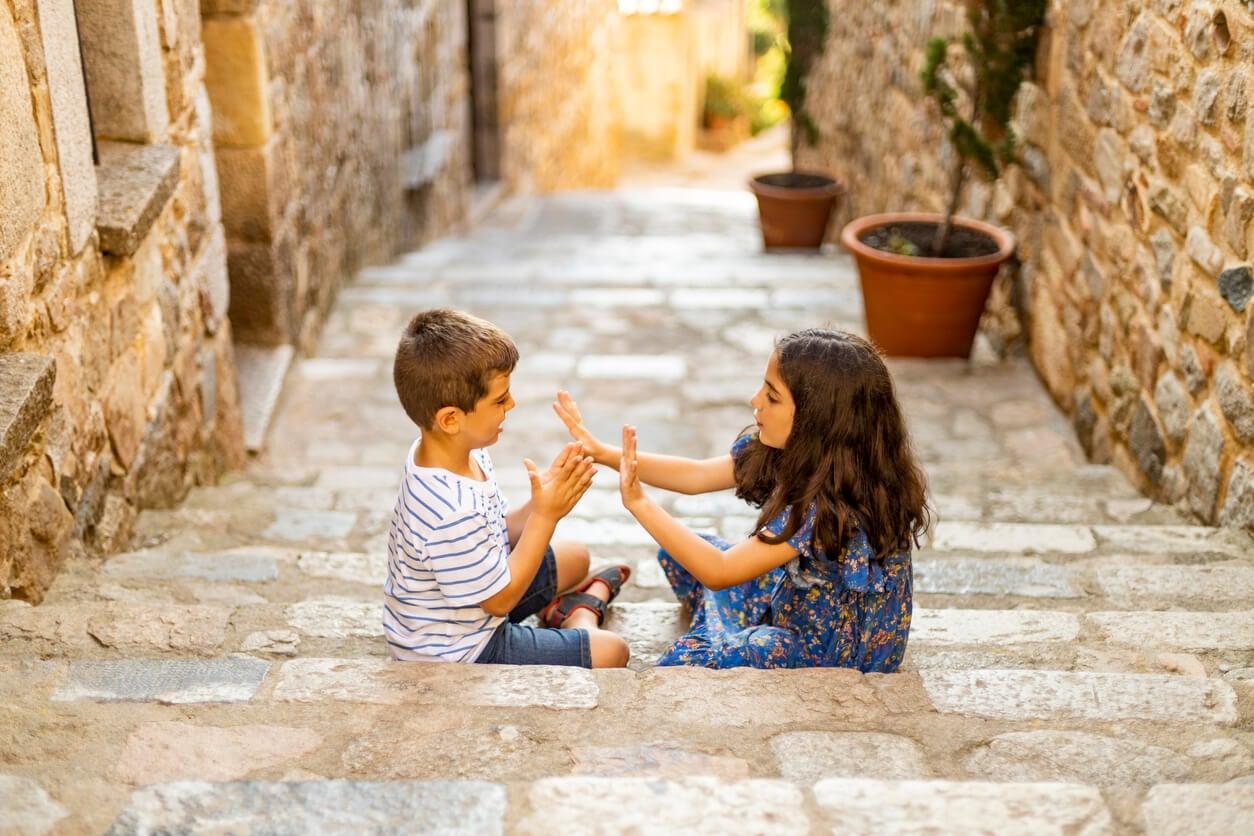 Niña y niño jugando a las palmas en la calle.