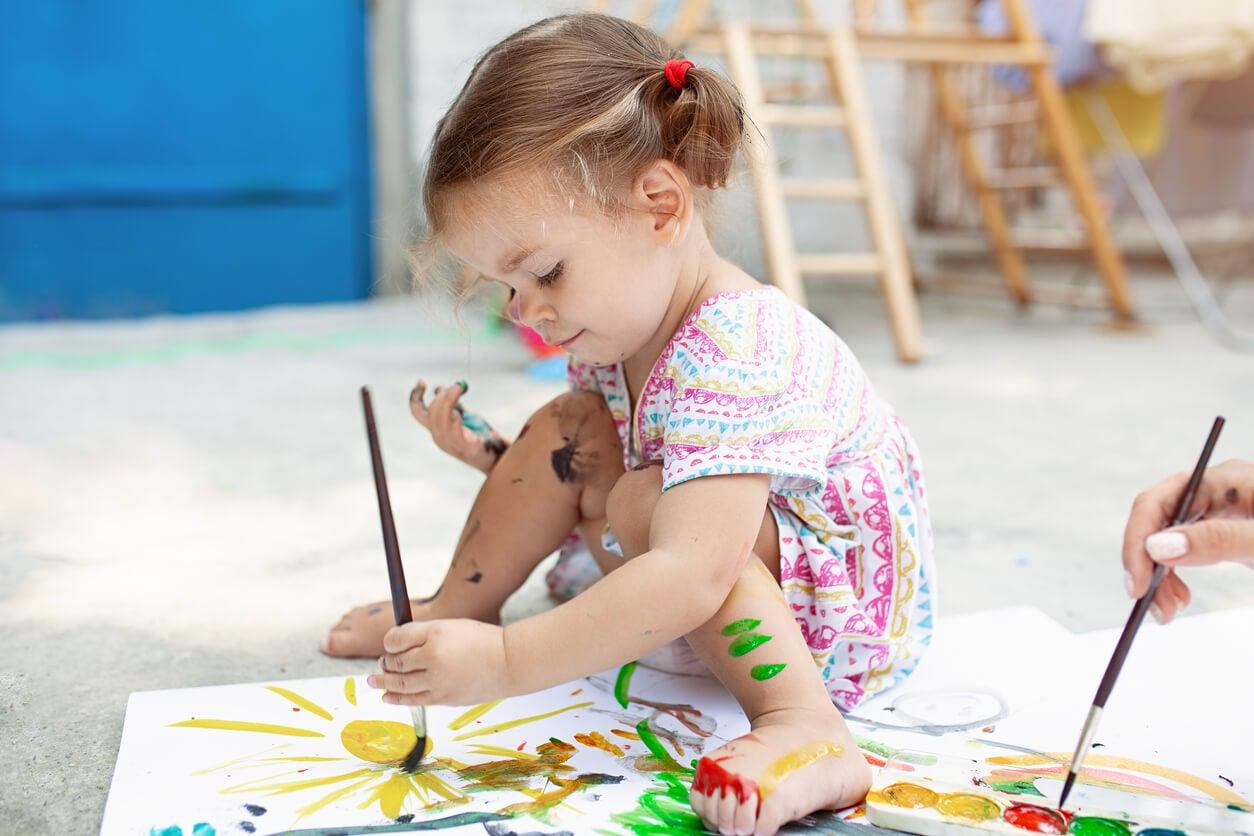 Niña pintando y explorando su creatividad.