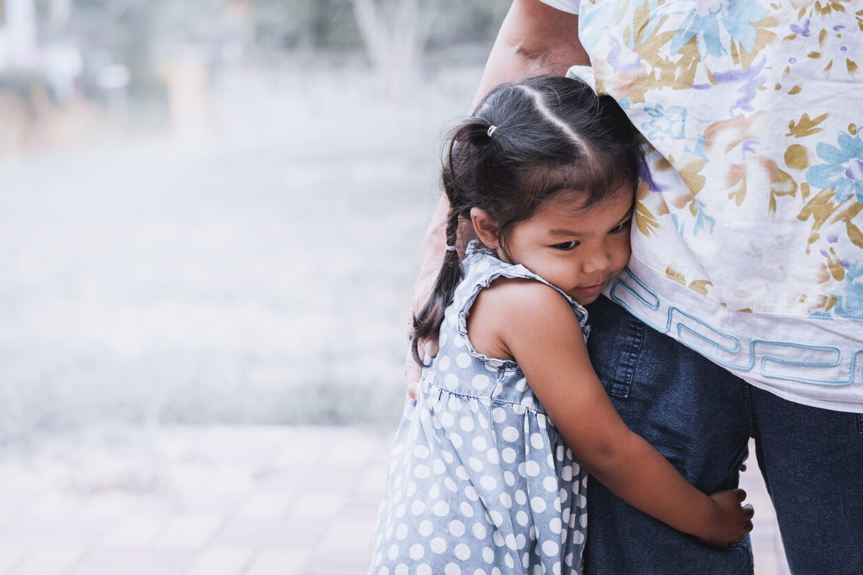 Une jeune fille qui entoure de ses bras la jambe d'un adulte.