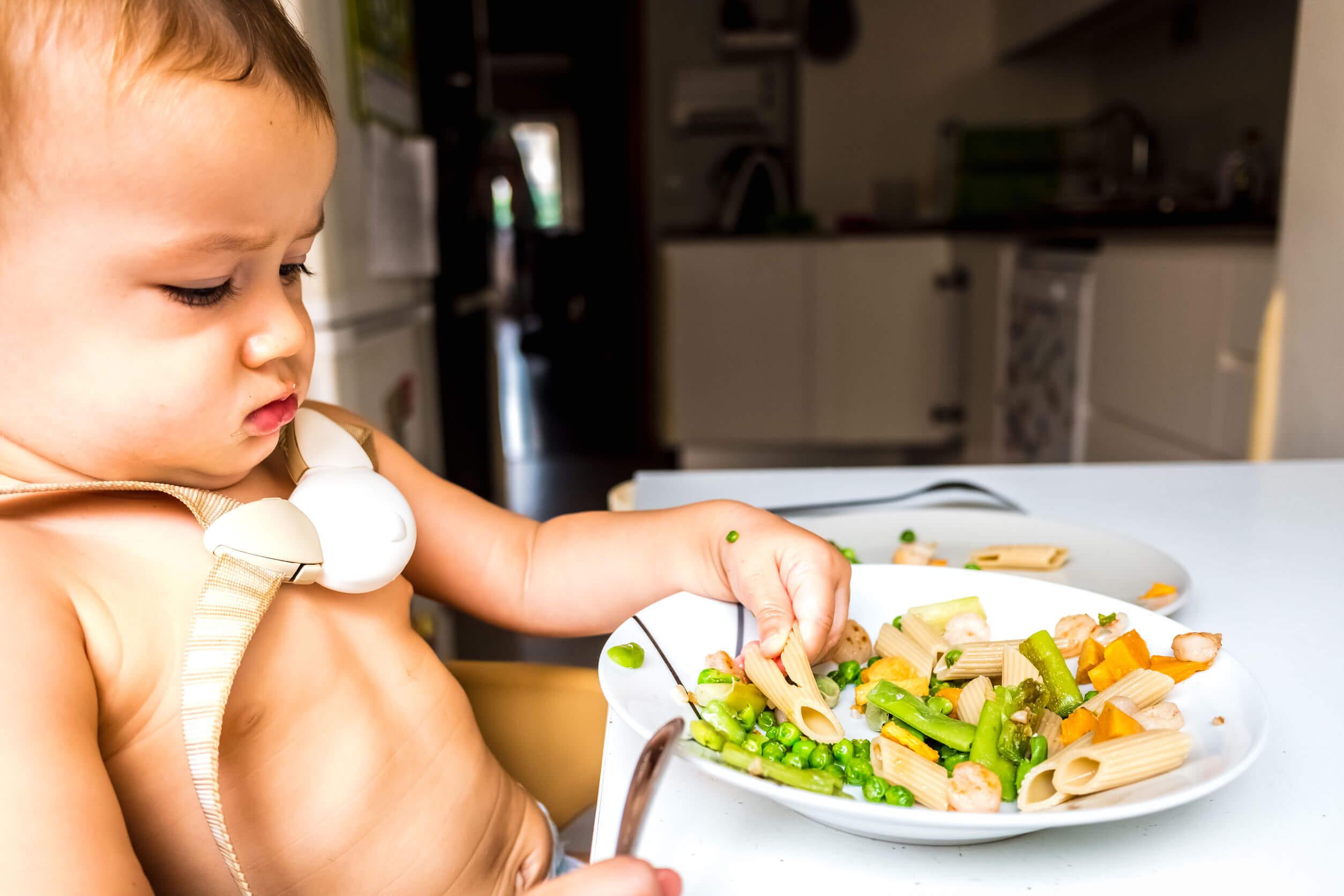 Niño aprendiendo a comer solo para evitar problemas de masticación.