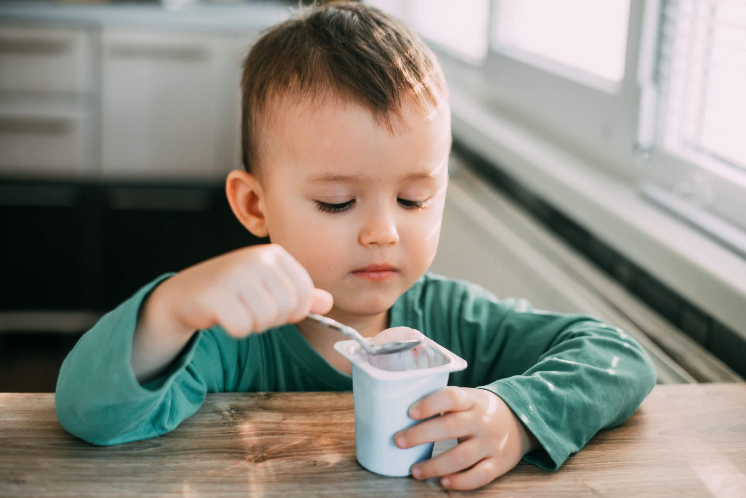 Niño comiendo yogur para aliviar el estreñimiento.