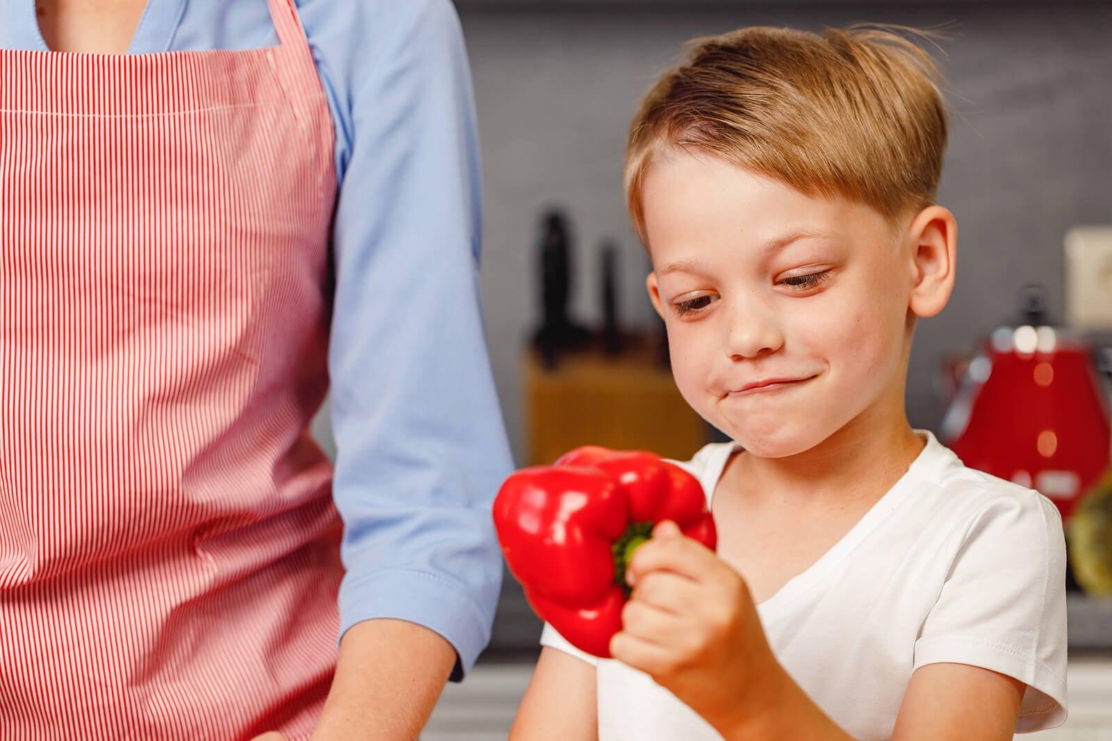 Bambino con un peperone rosso in cucina.