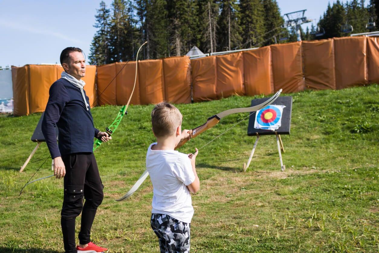 Niño practicando tiro con arco con su entrenador.