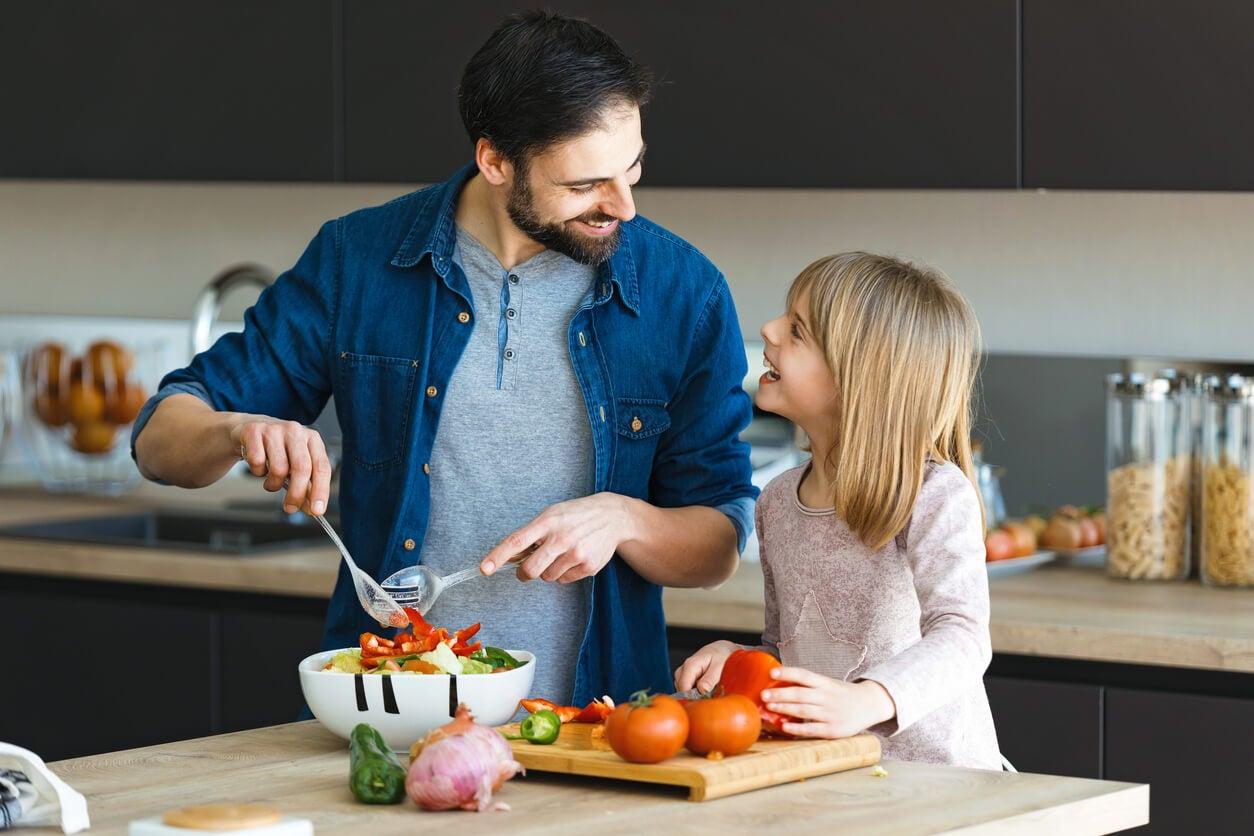 Père et fille cuisiner des aliments sains.