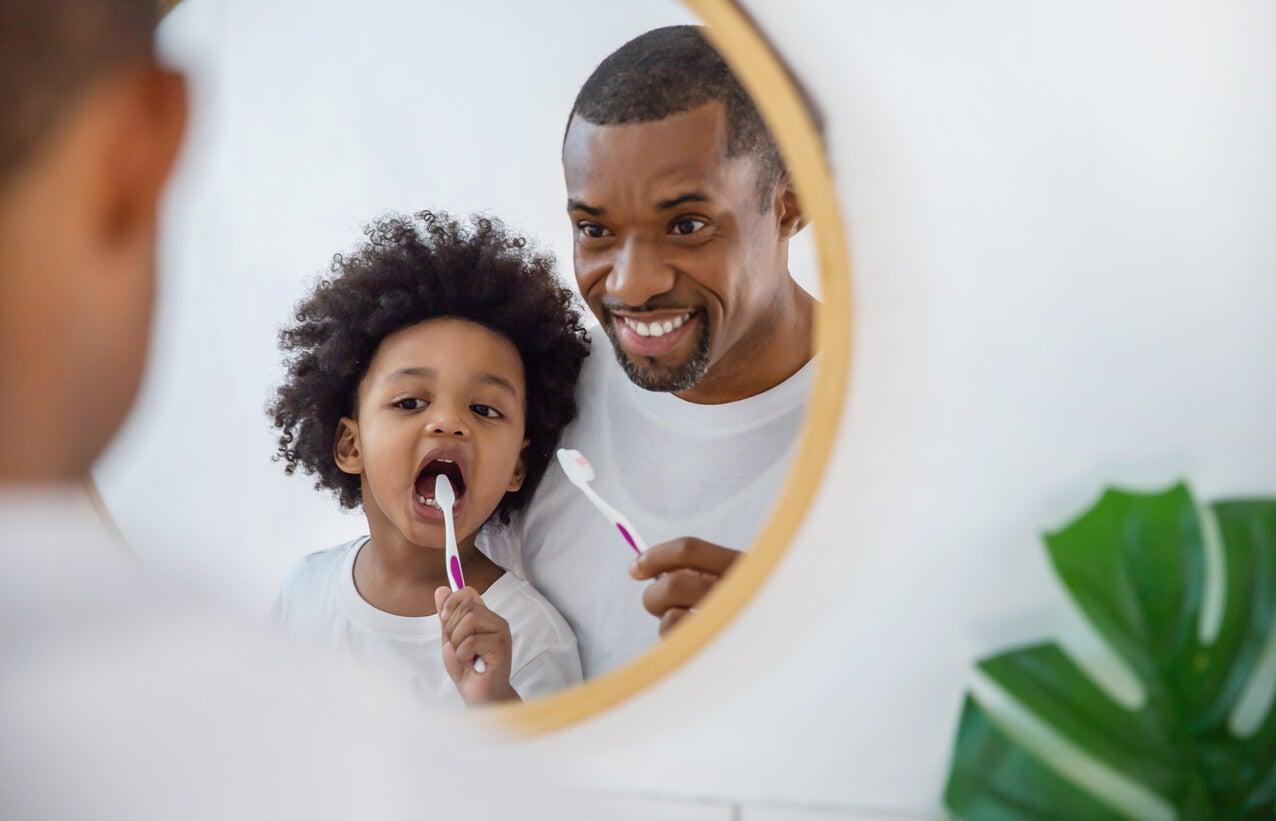 Padre con su hijo enseñando a su hijo a cepillarse los dientes y los diferentes cepillos de dientes para niños.