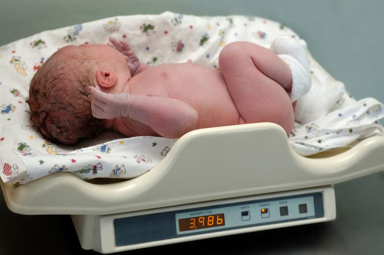 Bebé recién nacido en una báscula para calcular medicación