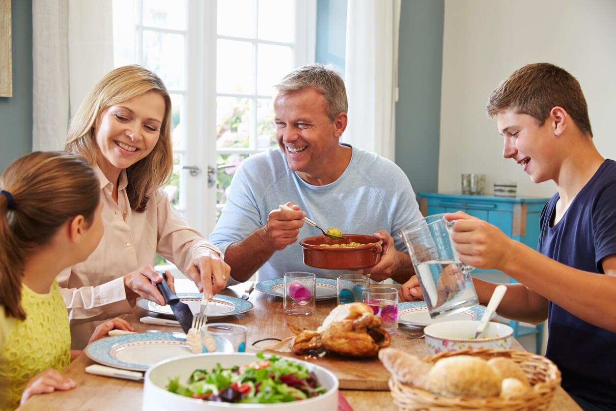 Familia comiendo con sus hijos teniendo en cuenta la alimentación infantil por etapas.