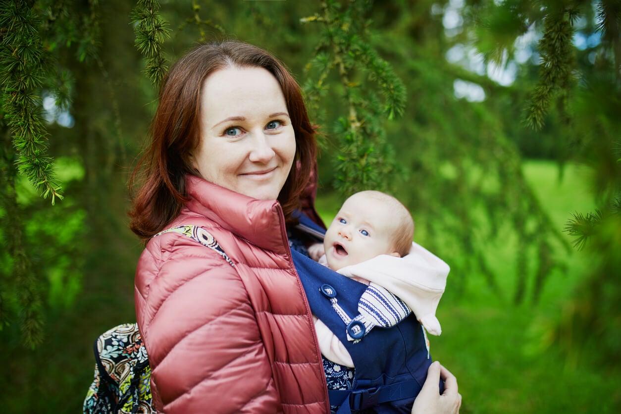 Une mère avec son bébé en sac de portage.