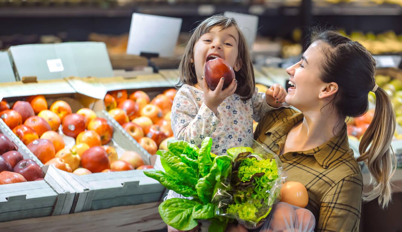 Madre con su hija en el supermercado para enseñarle a comer bien.