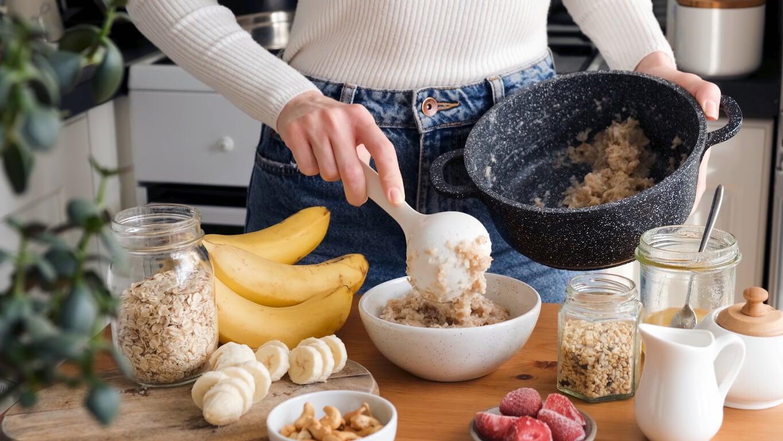 Mujer preparando un porridge de avena y frutas durante el primer trimestre del embarazo.