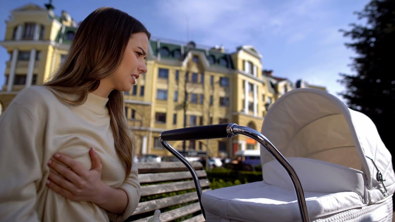 Une femme, avec son bébé, en plein air souffrant de douleur dans les seins.