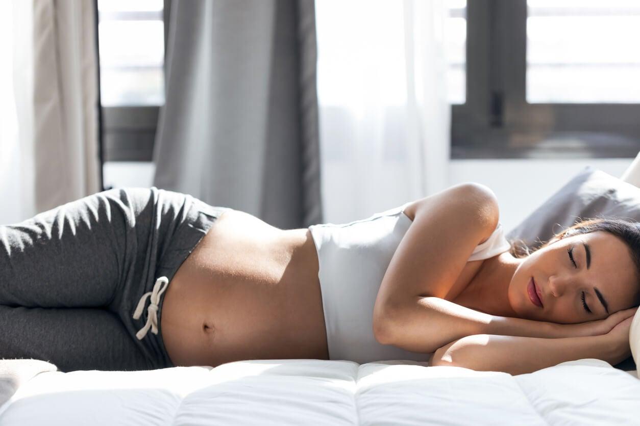 Mujer embarazada durmiendo la siesta debido a los cambios en el sueño.