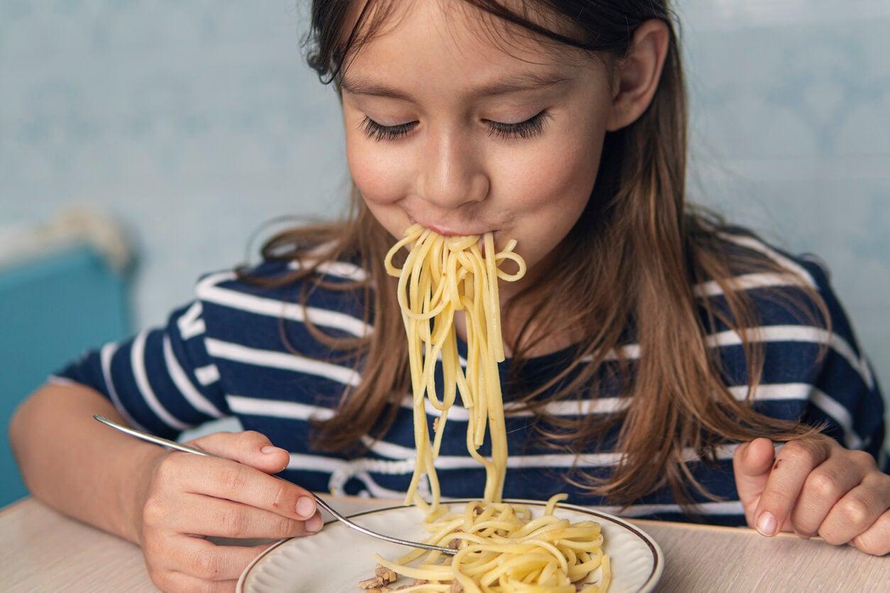 Niña comiéndose un plato de pasta, uno de los alimentos que parecen saludables, pero no lo son.