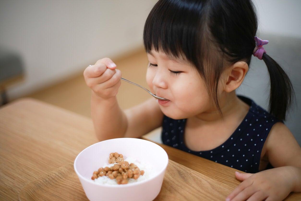 Niña comiendo arroz y legumbres.