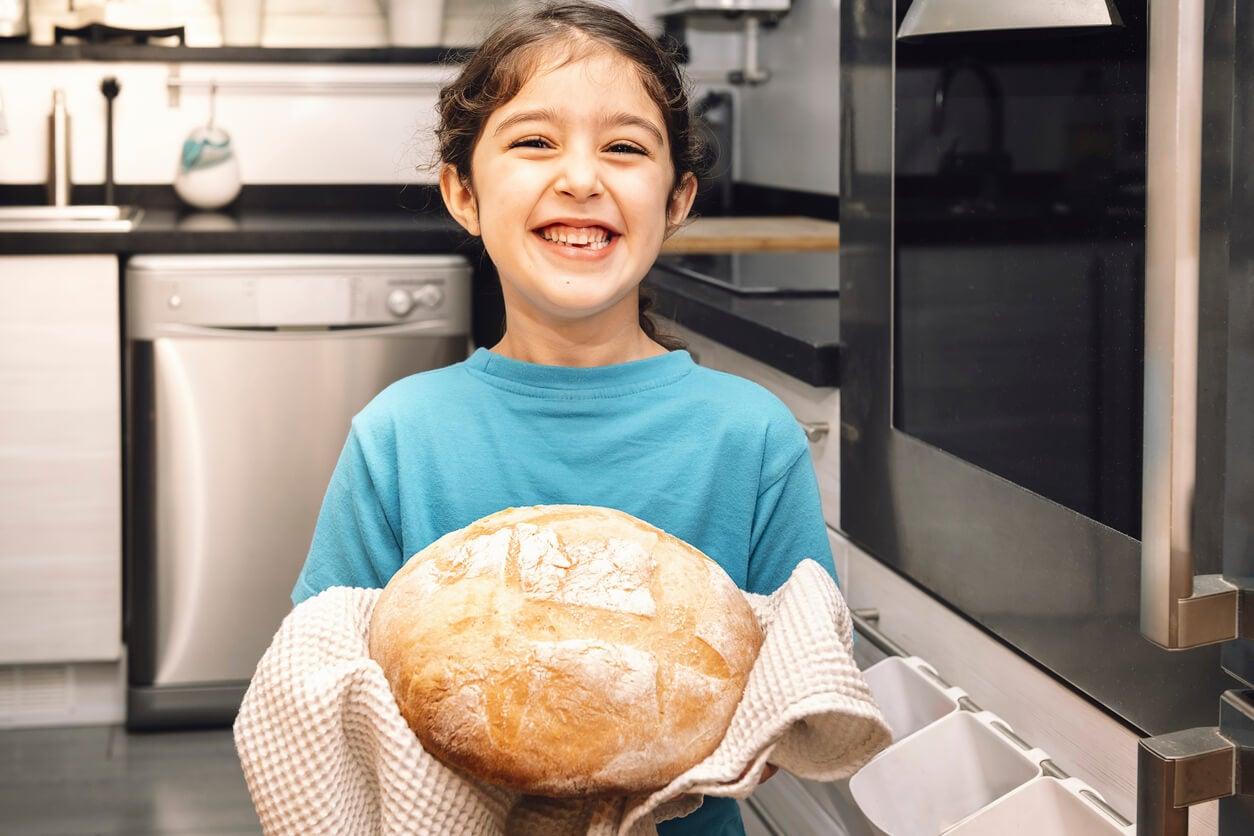 Niña sacando del horno un pan casero para aprovechar sus beneficios.