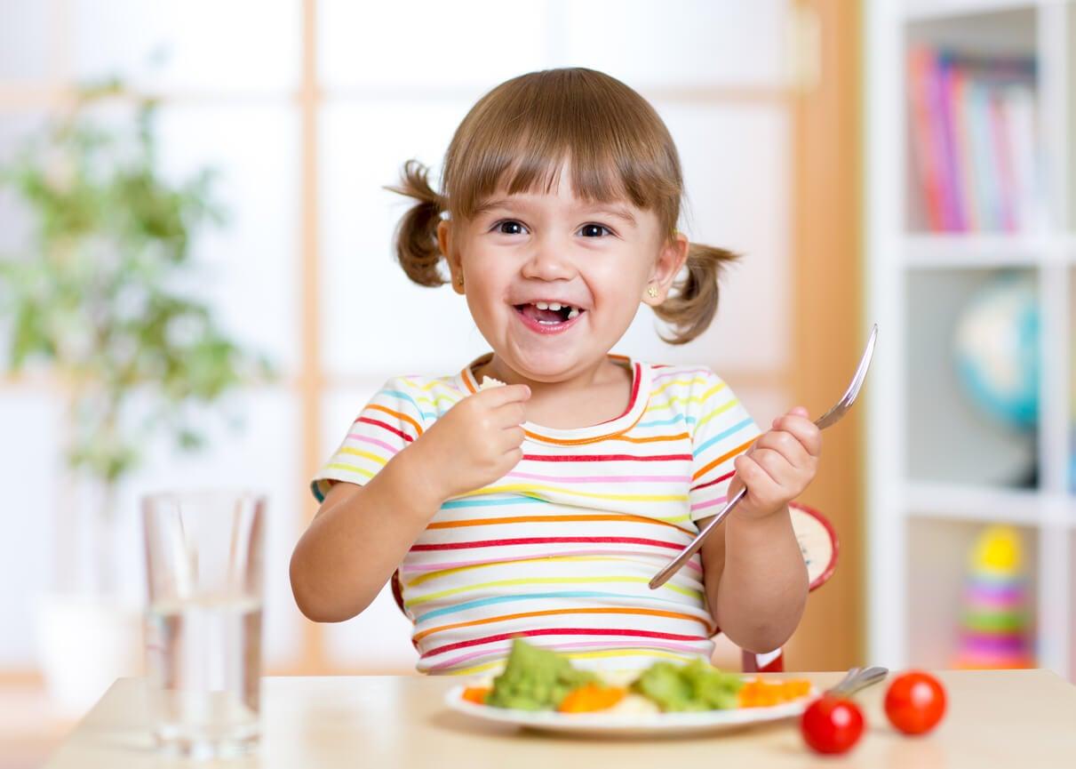 Niña comiendo de manera saludable.
