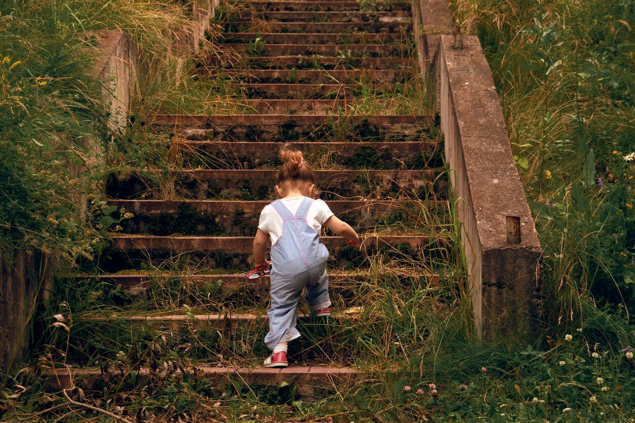 Niña subiendo unas escaleras enormes para aprender a no rendirse.