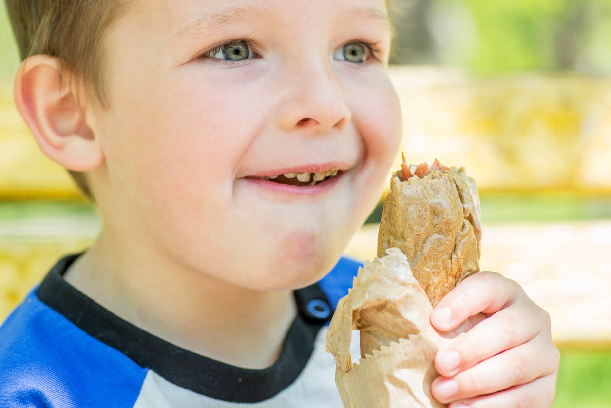 Niño comiendo un bocadillo con pan integral.