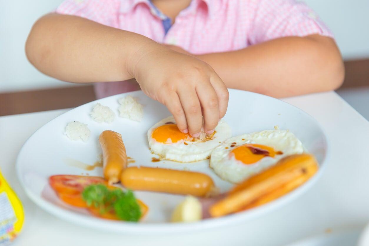 Niño comiendo huevos con salchichas.
